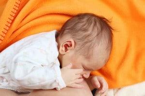 Säugling nuckelt an Brust