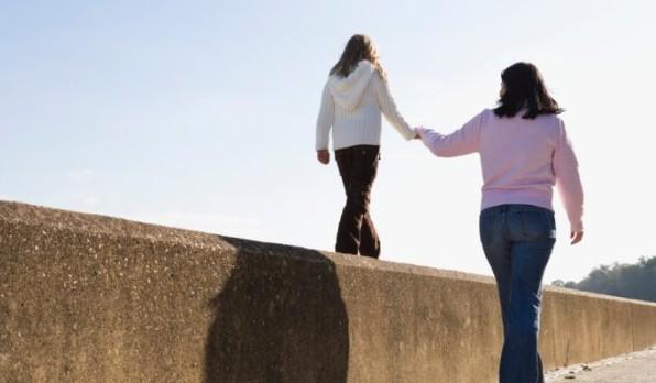 Vorsichtige Mutter stützt Kind beim Balancieren