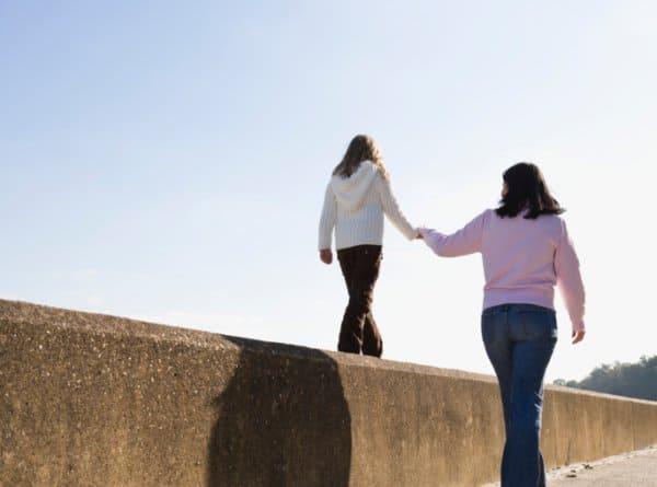 Mutter stützt Kind beim Balancieren