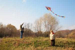 Kinder im Herbst mit Drachen im Freien