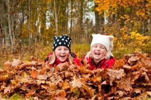 Mädchen spielen im Laub