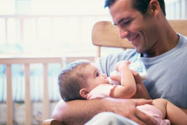 Papa fütter Baby mit Milch im Fläschchen