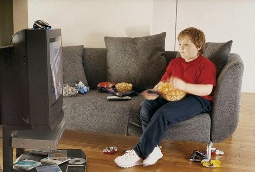 Übergewichtiger Junge vor dem Fernseher