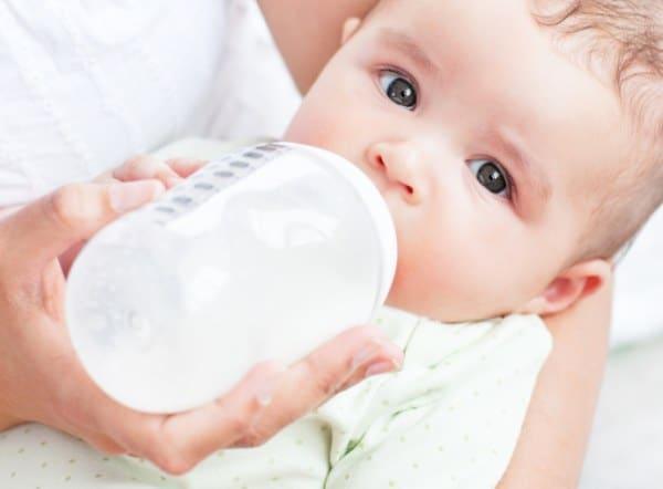 Mutter füttert Baby mit Pre-Milch aus Babyfläschchen