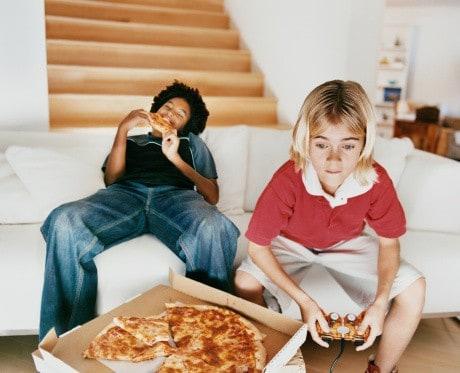 Kinder beim Videospielen mit Pizza
