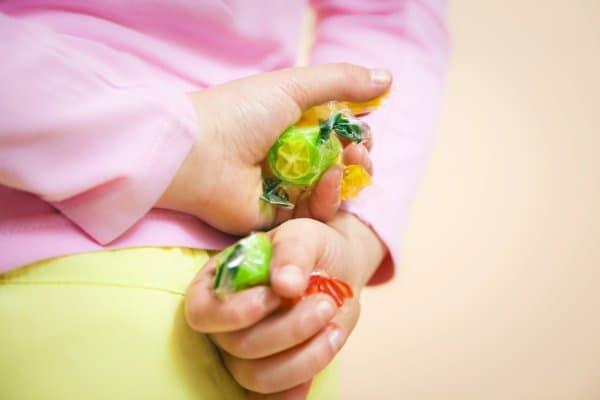 Kind lügt, versteckt Bonbons hinter dem Rücken. Ergebnis von Pinoccio Parenting?