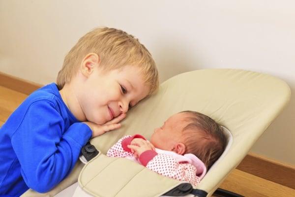 Großer Bruder bestaunt kleine Schwester (© Thinkstock)