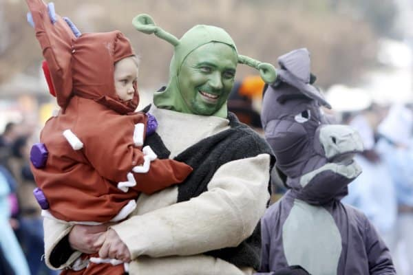 Mit Kind zum Karnevalsumzug - Vater und Baby als Shrek und Käfer kostümiert (© IdealPhoto30 / istock Editorial)