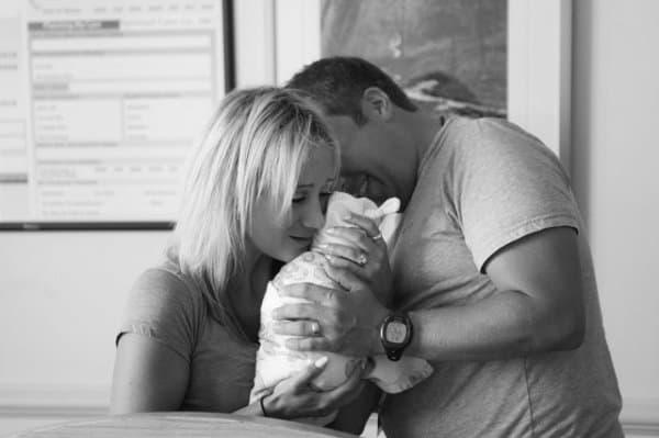Adoptivbaby kuschelt mit Mama und Papa