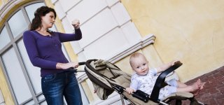 Mother looking at watch with baby in stroller outdoors