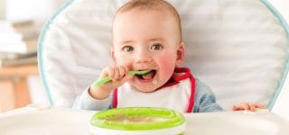 Baby boy in high chair feeding himself with spoon