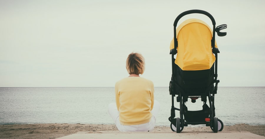 Warum sich immer mehr Mütter allein fühlen - Mutter mit Kinderwagenallein am Strand (© stock.adobe.com)